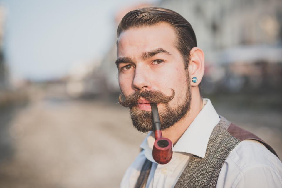 Mężczyzna używający wosku do wąsów.