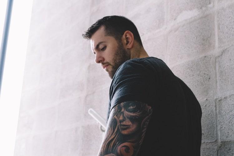 Mężczyzna z tatuażami tyłem